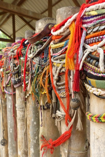 Bracelets hanging on fence around mass grave at Choeung Ek Killing Fields, Phnom Penh, Cambodia