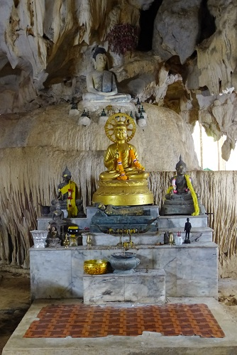 Golden Buddha in a cave with flowstone features at the Tiger Cave Temple, Krabi, Thailand