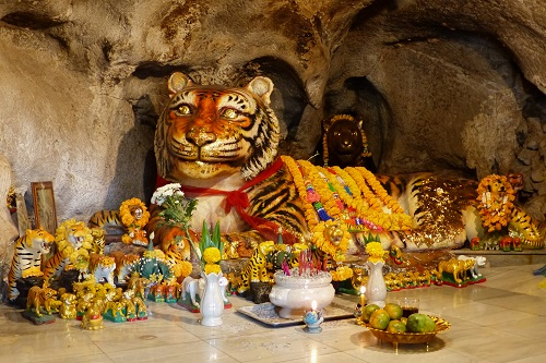 Tiger statue festooned with marigolds at the Tiger Cave Temple, Krabi, Thailand
