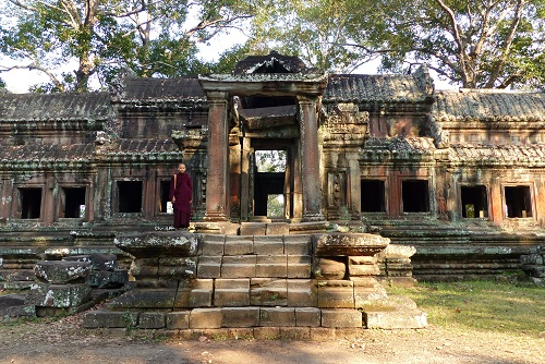 Monk standing on East Gate of Angkor Wat temple near Siem Reap, Cambodia