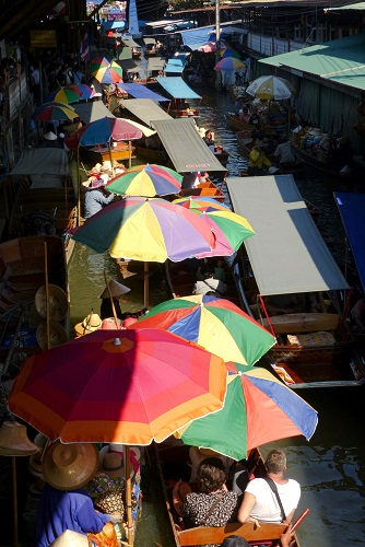 Boats with umbrellas on the crowded canal at Damnoen Saduak Floating Market, Thailand