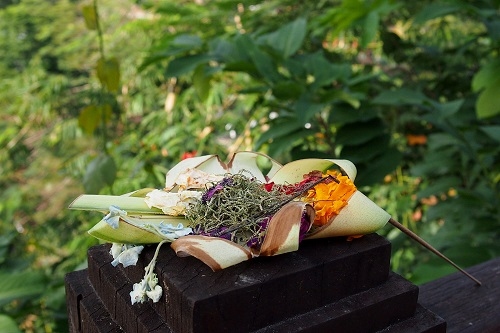 Canang sari Balinese offering on fence post in Bali, Indonesia