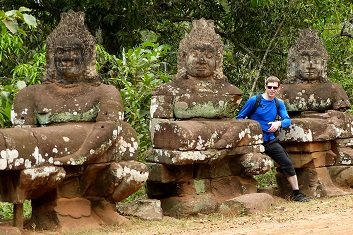 Man standing with statues of demons at Angkor Thom, Siem Reap, Cambodia