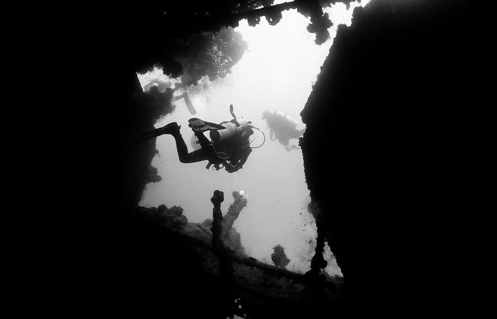 Silhouetted divers leaving the engine room of the Yamagiri Maru wreck in Chuuk Lagoon, Micronesia
