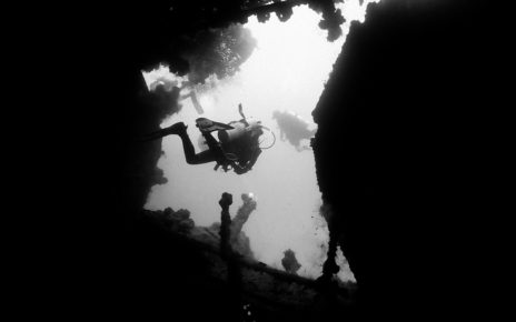 Silhouetted divers leaving the engine room of the Yamagiri Maru wreck in Chuuk Lagoon, Micronesia