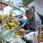 Lady selling fruit from a boat at Damnoen Saduak Floating Market in Thailand