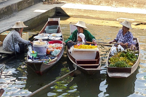 Locals in boats at Damnoen Saduak Floating Market, Thailand