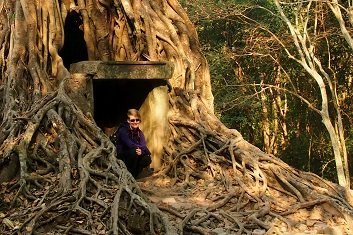 Woman sitting by temple engulfed in strangler fig roots at Sambor Prei Kuk, Cambodia