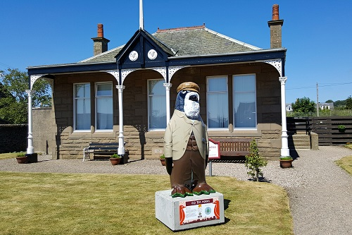 Penguin statue dressed as old man with beard in front of golf club, Carnoustie, Scotland