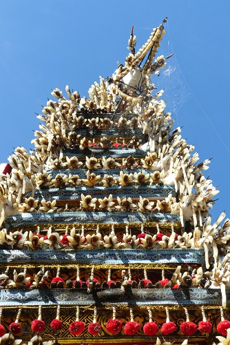 Balinese offering pyramid decorated with carved pork rind and pom poms in Pejeng, Bali, Indonesia
