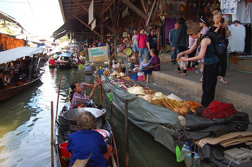 Purchasing fried bananas from a boat at Damnoen Saduak Floating Market, Thailand