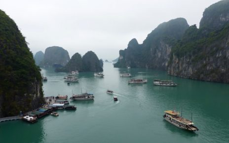 Cruise boats and limestone karst seen from Sung Sot Cave in Halong Bay, Vietnam
