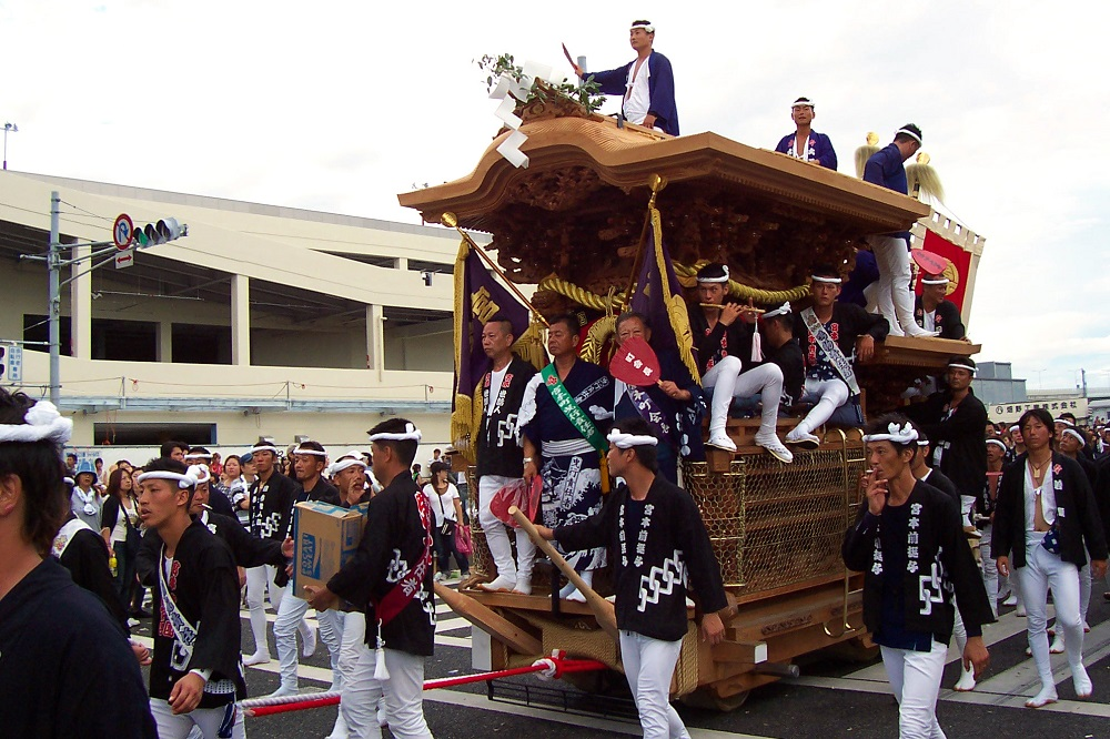 Men in traditional happi coats pulling wooden float at Kishiwada Danjiri in Osaka, Japan