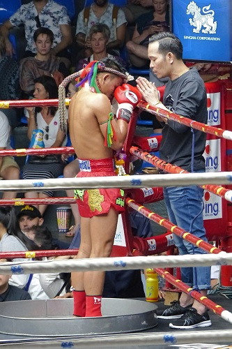 Muay Thai fighter prays with his coach, Bangkok, Thailand