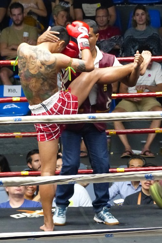 Coach assisting with Muay Thai fighters stretches in Bangkok, Thailand