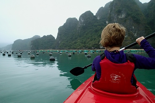 Girl kayaking around pearl farm buoys in Halong Bay, Vietnam
