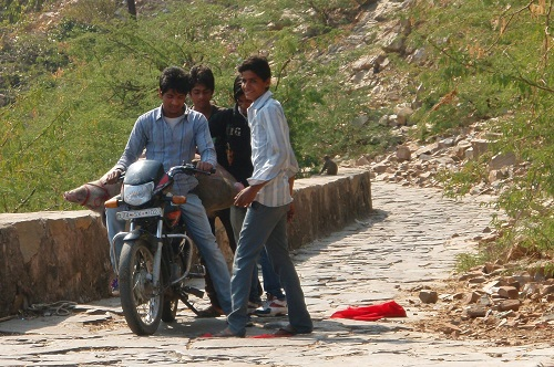 Boys on motorbike with hog-tied pig near Galtaji in Jaipur, India