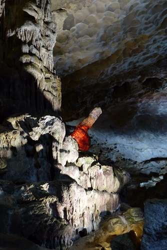 Phallic rock glowing red at Sung Sot Cave in Halong Bay, Vietnam