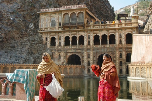 Two ladies washing clothes in the holy water tank at Galtaji Temple near Jaipur, India