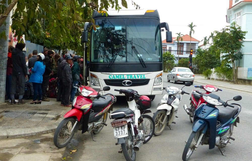 Camel Travel bus and scooters parked at roadside in Hoi An, Vietnam