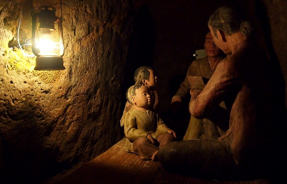 Figures of people sitting in a dimly lit cave at Vinh Moc Tunnels in Vietnam