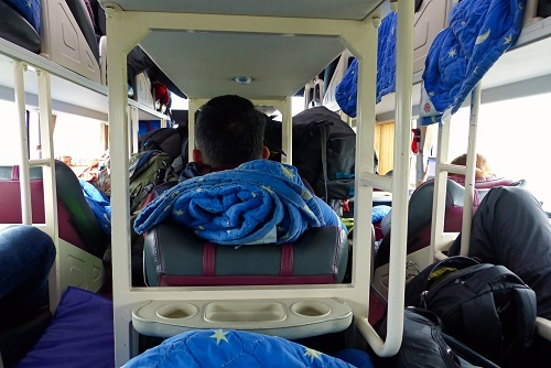 Crowded Camel Travel bus with luggage stacked in aisles near Hoi An, Vietnam
