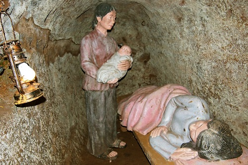 Midwife and baby standing over mother in cramped maternity room at Vinh Moc Tunnels in Vietnam