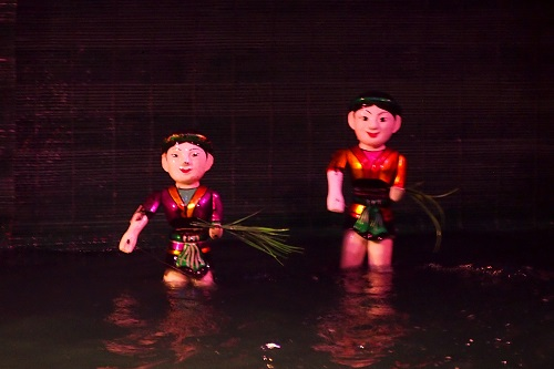 Two farmers carrying bundles of rice at Thang Long Water Puppet Theatre in Hanoi, Vietnam