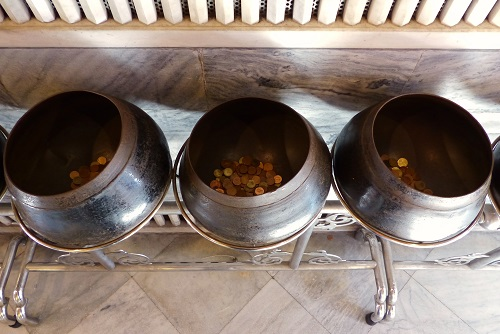 Row of begging bowls and coins at Wat Pho temple in Bangkok, Thailand