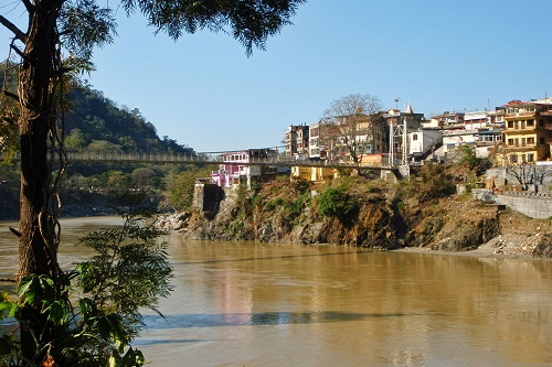 Lakshman Jhula bridge crossing muddy Ganges river in Rishikesh, India