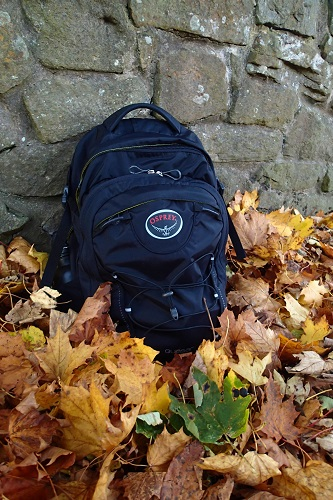 Travelling light with a black osprey backpack sitting on autumn leaves