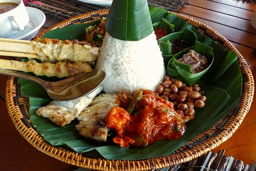 Megibung platter with skewers, sambal, nuts, meat and rice ready to eat in Bali, Indonesia