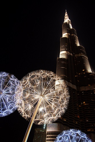 Burj Khalifa at night with dandelion sculptures in front in Dubai, UAE