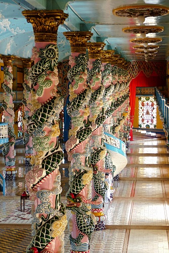 Dragons coiled around columns inside Cao Dai Holy See temple in Vietnam