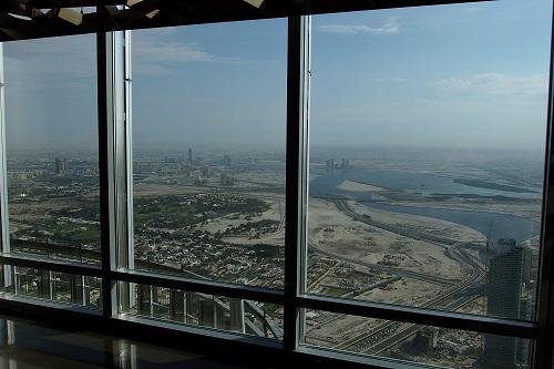 Huge windows with view across the desert from the Burj Khalifa in Dubai, UAE