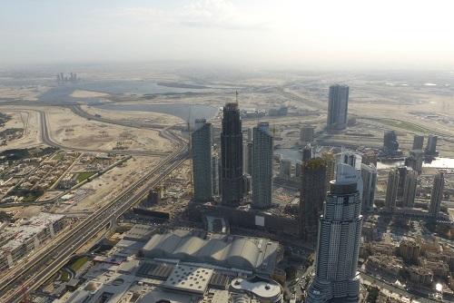 View across skyscrapers to the desert beyond from the Burj Khalifa in Dubai, UAE