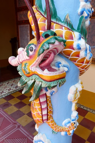Dragon coiled around a pillar at Cao Dai Holy See temple in Vietnam