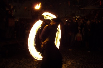 Fire dancer twirling flaming cannonball at Esslingen Medieval Market in Germany