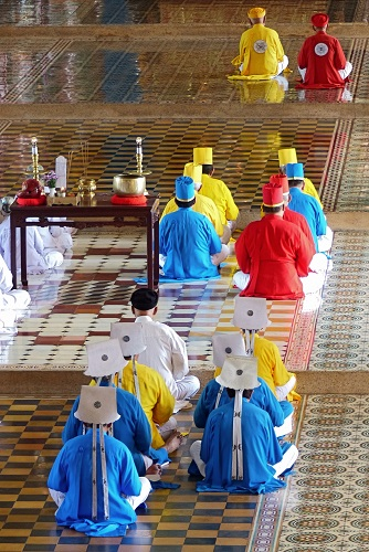 Priests in coloured robes at Cao Dai Holy See temple in Vietnam