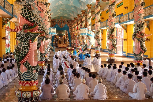 Rows of worshippers at Cao Dai Holy See temple in Vietnam
