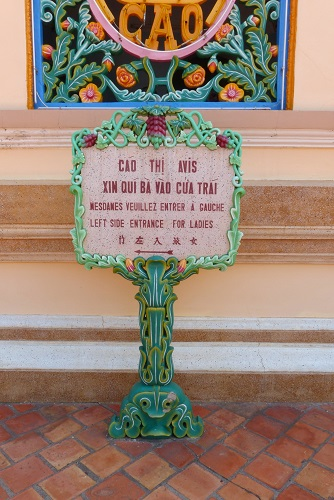 Sign to ladies entrance at Cao Dai Holy See temple in Vietnam