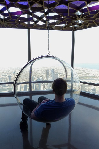 Man sitting in hanging perspex ball admiring view over Dubai from the Burj Khalifa in UAE
