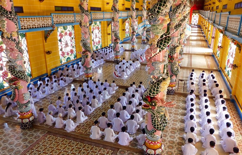 Worshippers in white sitting on floor of Cao Dai Holy See in Vietnam