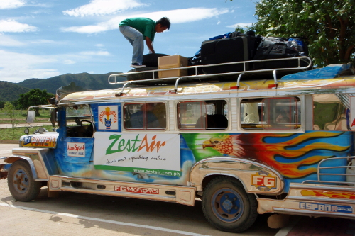 Man loading luggage onto a jeepney in Coron, Philippines