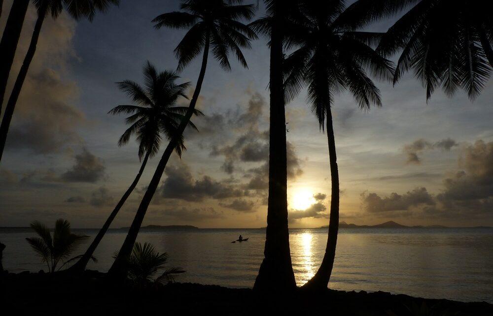 Paddling canoe and palm trees at dusk in Chuuk Lagoon, Micronesia