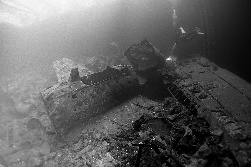 Diver swimming over Zero fighter planes on Fujikawa Maru wreck in Chuuk Lagoon, Micronesia