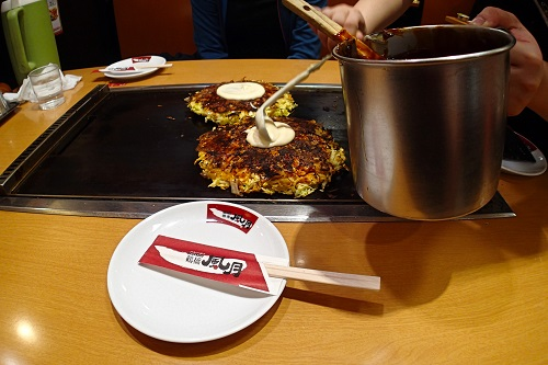 Spreading mayo on okonomiyaki, Osaka food in Japan