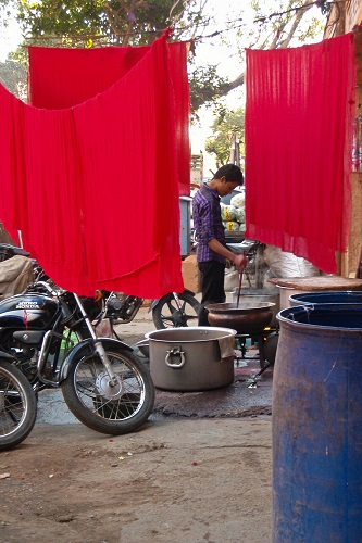 Man dyeing cloth red in the Pink City in Jaipur, India
