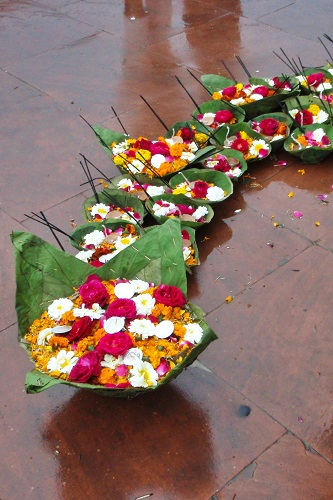 Row of floral diya offerings for sale at Ganga Aarti in Haridwar, India