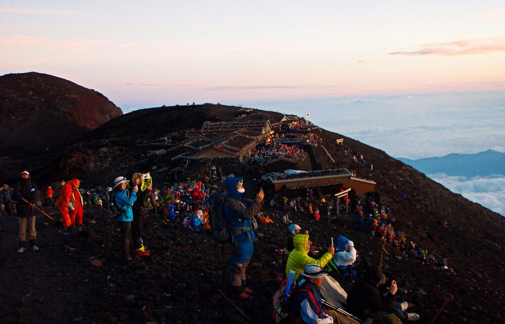 Crowds watching sunrise from summit of Mount Fuji, Japan
